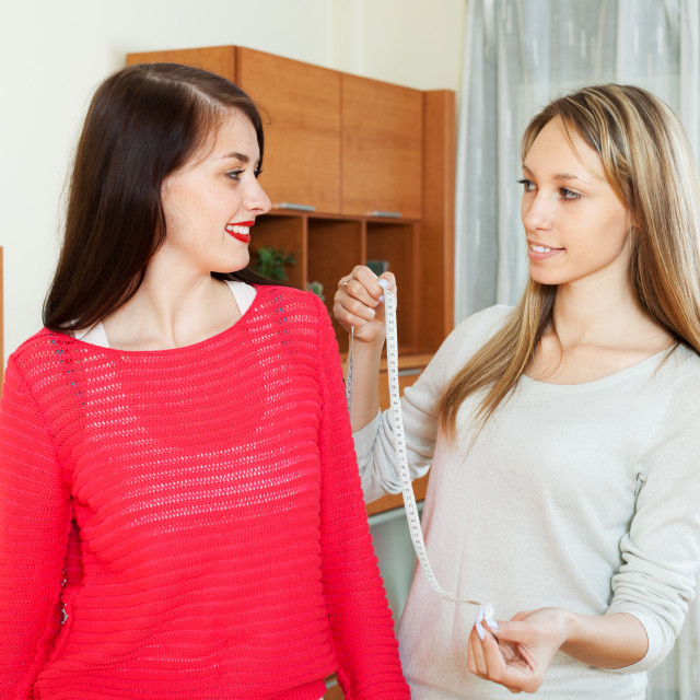 """Two smiling girlfriends measuring with measuring tape"" stock image"
