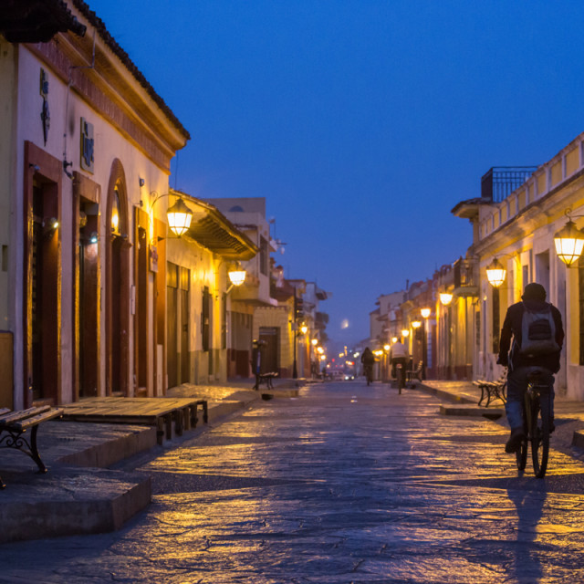 """""""A cyclist travels though the cobbled roads of San Cristobal de las casas at dawn"""" stock image"""