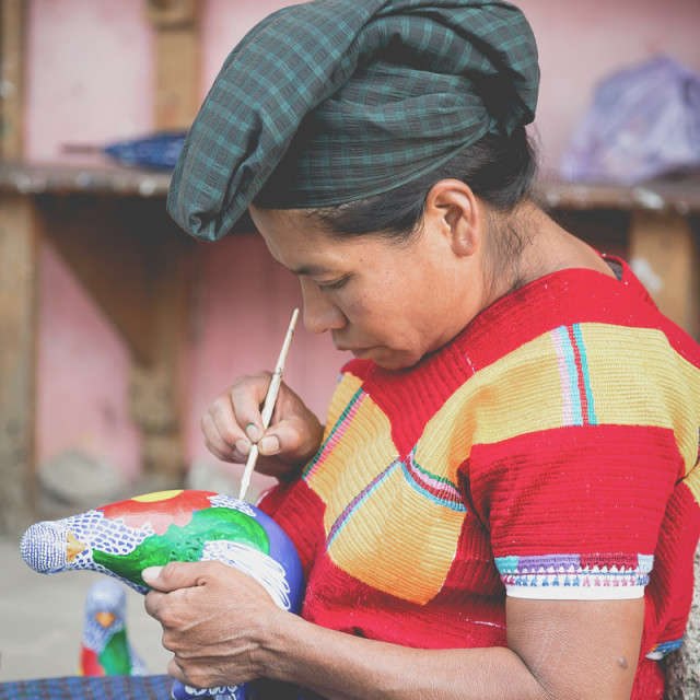 """""""Indigenous woman painting a clay bird in Chiapas"""" stock image"""