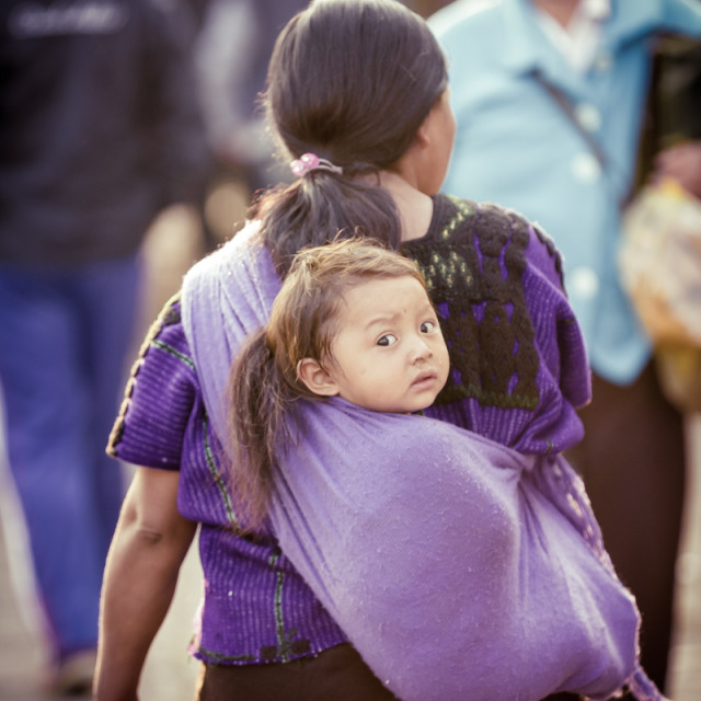 """Mexican Indigenous woman carrying her baby in a rebozo"" stock image"