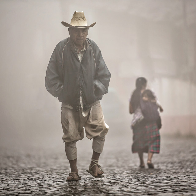 """Indigenous man walking along cobbled road on a hazy morning"" stock image"