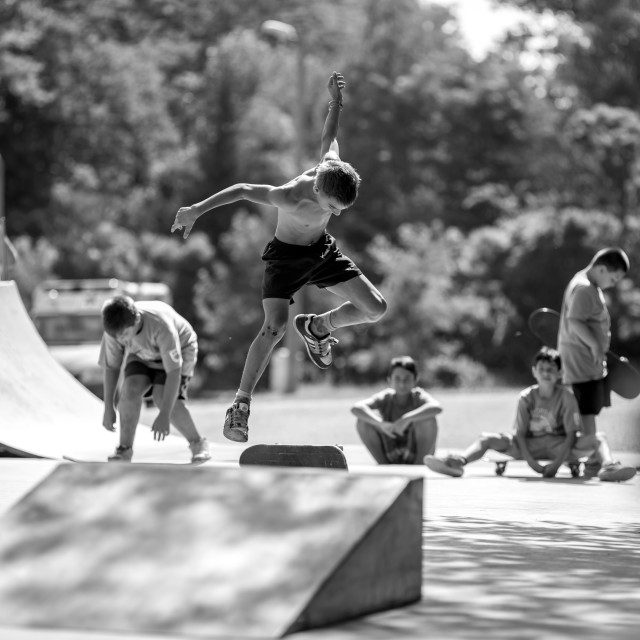 """Boy is making skate tricks behind a skate ramp"" stock image"