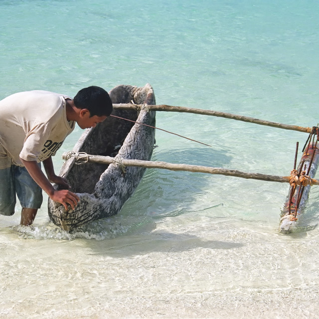 """""""a boy launches a wooden boat into the sea in Tonga"""" stock image"""