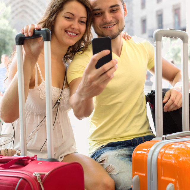 """Couple with luggage doing selfie"" stock image"