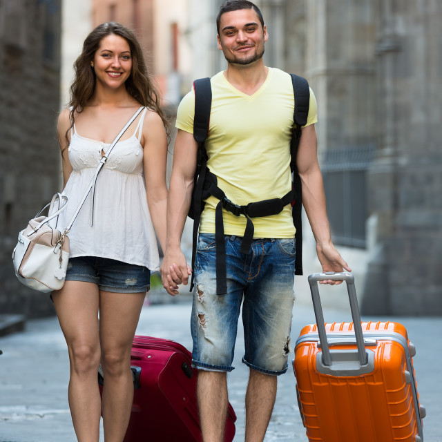 """""""couple in shorts with luggage walking through city"""" stock image"""