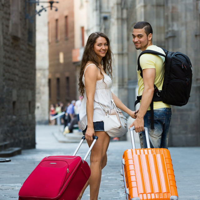"""Smiling couple in shorts walking through city"" stock image"