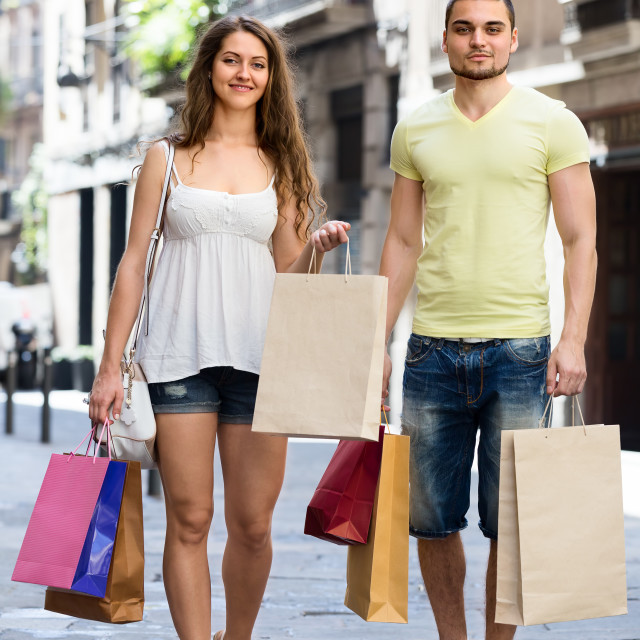 """smiling young pair with shopping bags at city"" stock image"