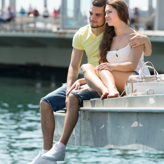 """Couple taking sunbath on the pier"" stock image"