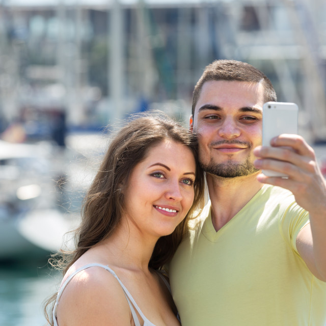 """Girl and guy taking selfie in city"" stock image"