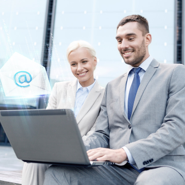 """""""smiling businesspeople with laptop sending e-mail"""" stock image"""