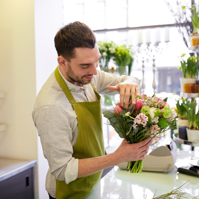 """smiling florist man making bunch at flower shop"" stock image"
