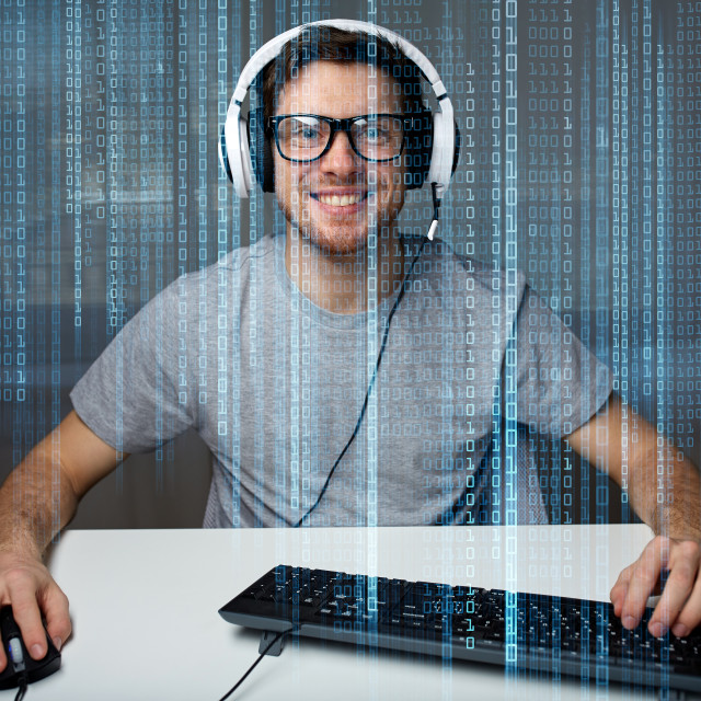"""man in headset playing computer video game at home"" stock image"