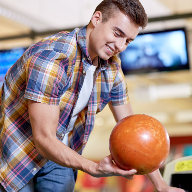 """""""happy young man holding ball in bowling club"""" stock image"""