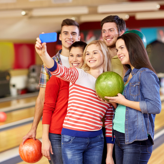 """""""happy friends with smartphone in bowling club"""" stock image"""
