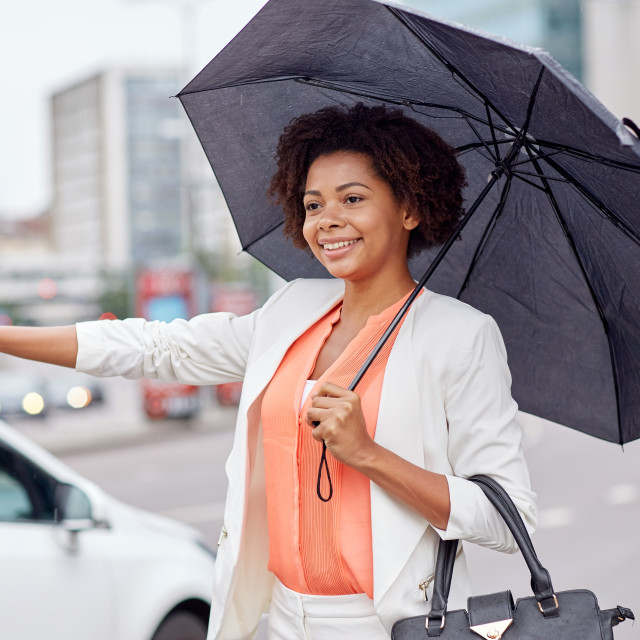 """""""happy african woman with umbrella catching taxi"""" stock image"""