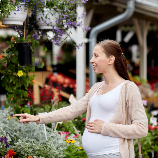 """pregnant woman choosing flowers at street market"" stock image"