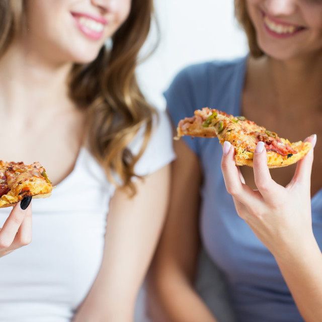 """""""happy friends or teen girls eating pizza at home"""" stock image"""