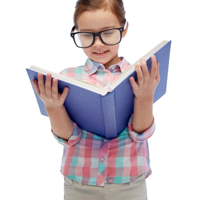 """happy little girl in eyeglasses reading book"" stock image"