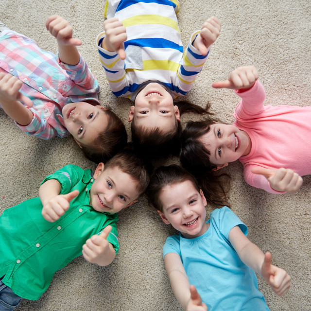 """""""happy kids lying on floor and showing thumbs up"""" stock image"""