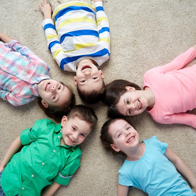 """happy smiling little children lying on floor"" stock image"