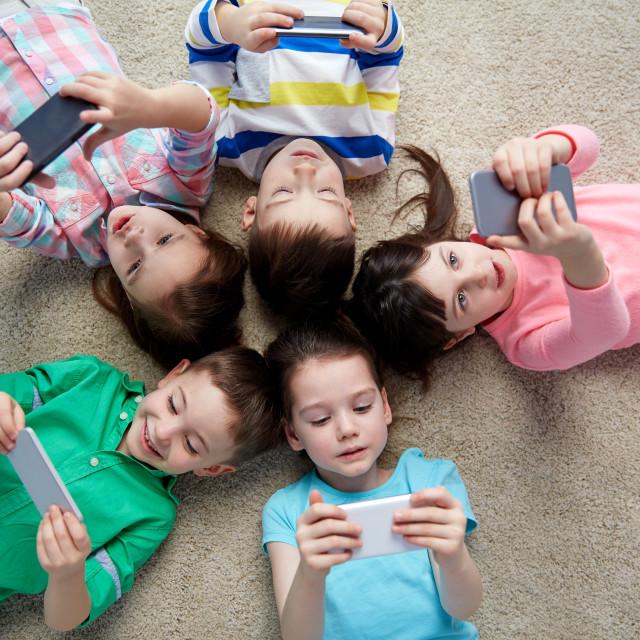 """""""happy children with smartphones lying on floor"""" stock image"""