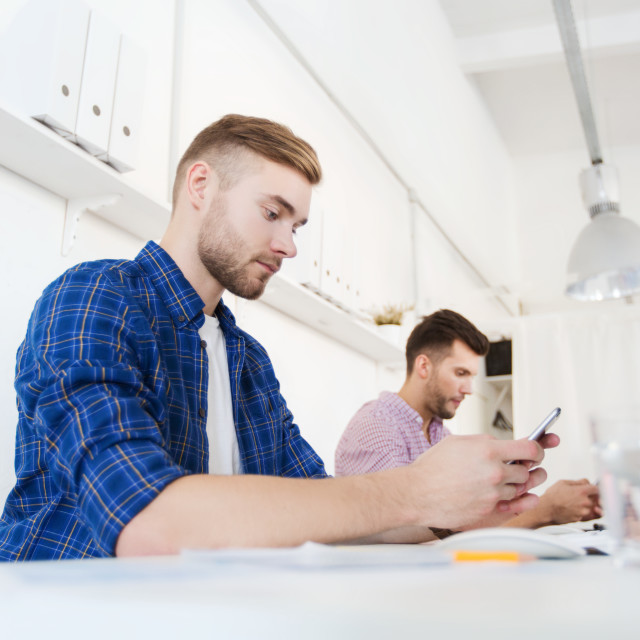 """""""creative man texting on cellphone at office"""" stock image"""