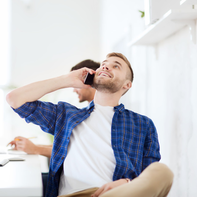 """""""happy creative man calling on cellphone at office"""" stock image"""