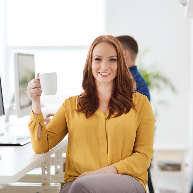 """""""happy woman drinking coffee or tea at office"""" stock image"""