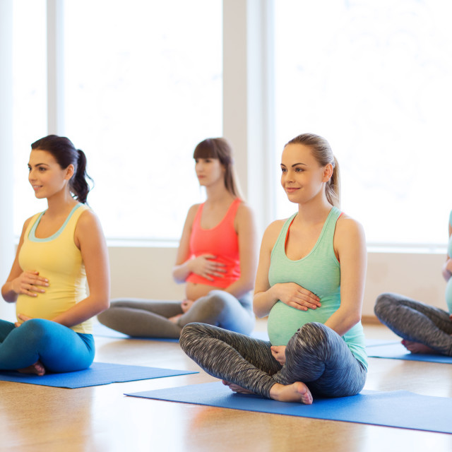 """happy pregnant women exercising yoga in gym"" stock image"