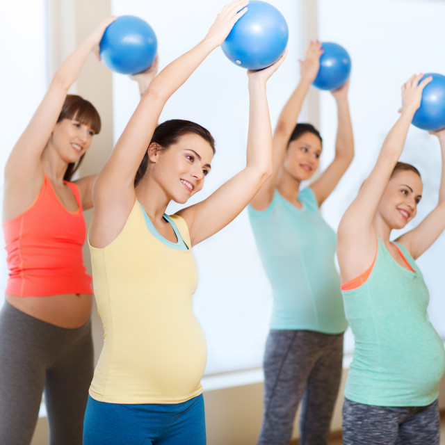 """""""happy pregnant women exercising with ball in gym"""" stock image"""