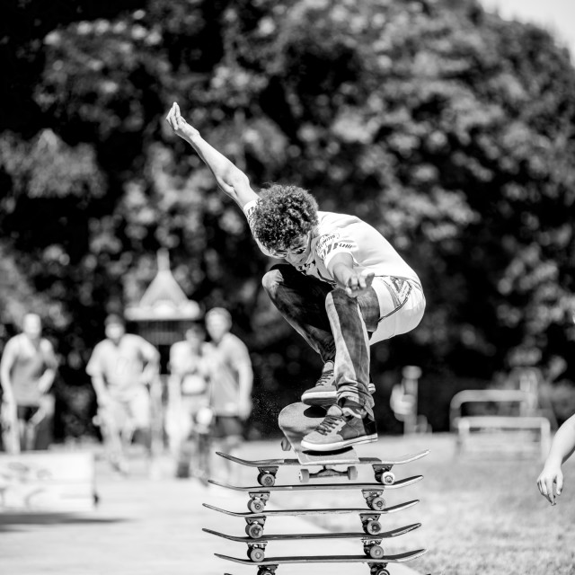 """Young sporty man with big curly hair jumping over stacked skate boards."" stock image"