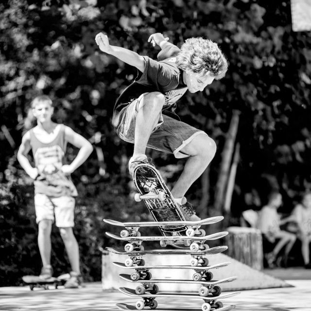 """Young man with curly hair jumping over stacked skate boards."" stock image"