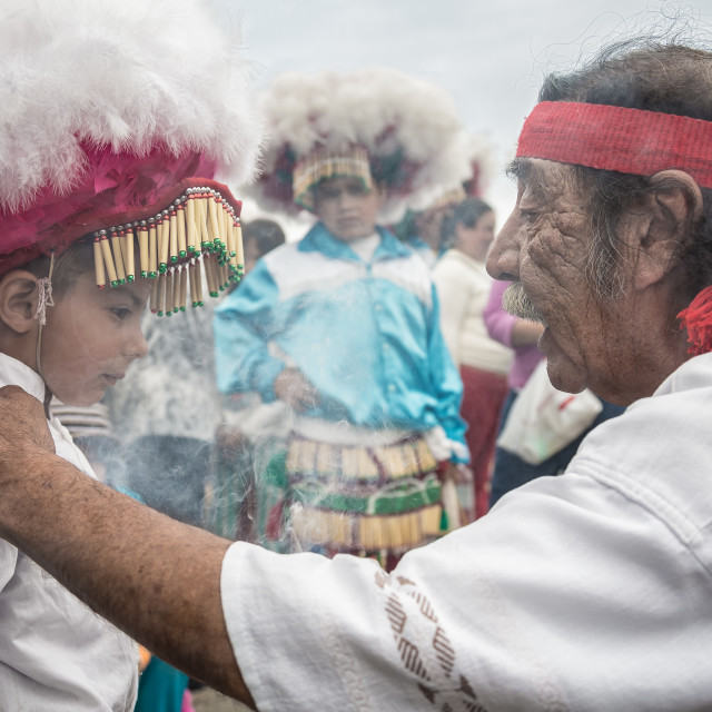 """An old spiritual healer talks to a traditionally dressed young boy in mexico"" stock image"