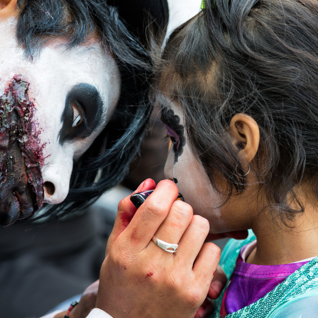 """A young man paints his daughters face for day of the dead celebrations in mexico"" stock image"