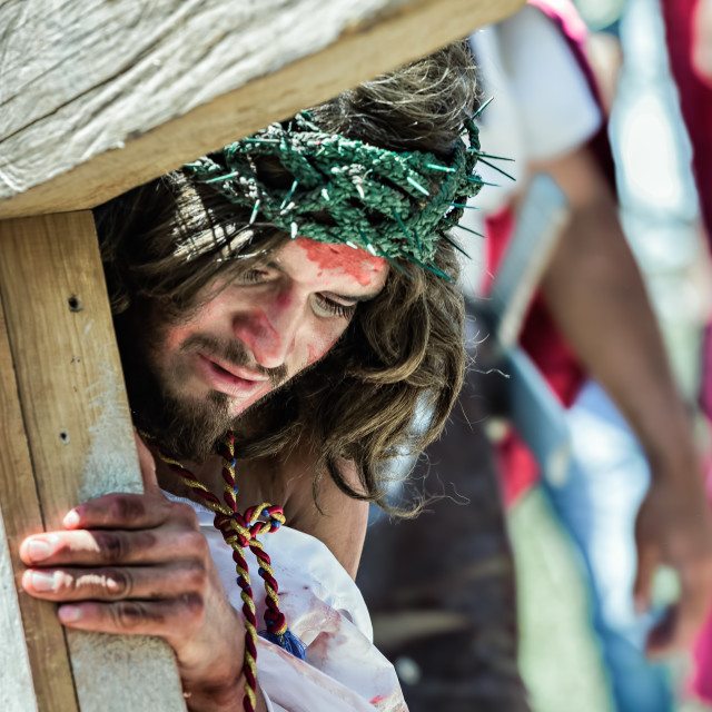 """A young man dressed as Jesus Christ carries a wooden cross through a village"" stock image"