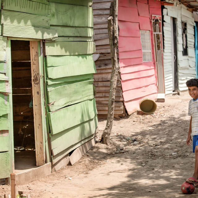 """A young boy stands with a football in a poor community in Barranquilla, Colombia"" stock image"