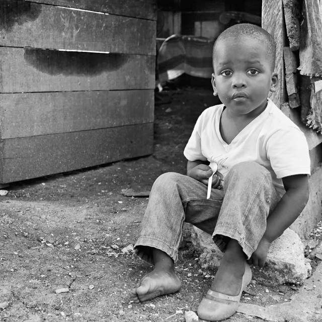 """A young afro carribean boy sits outside a slum in Cartagena in Colombia"" stock image"