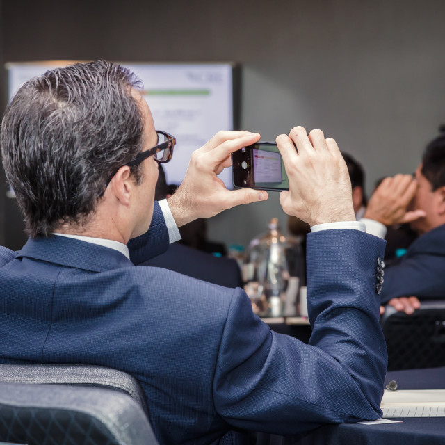 """""""A man takes a photo of a screen at a business presentation"""" stock image"""