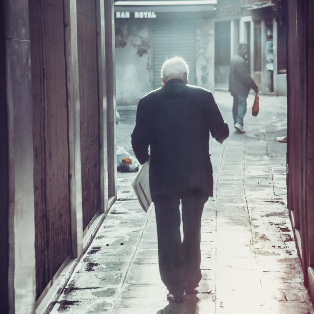 """an elderly man walks in the narrow streets of venice, Italy"" stock image"