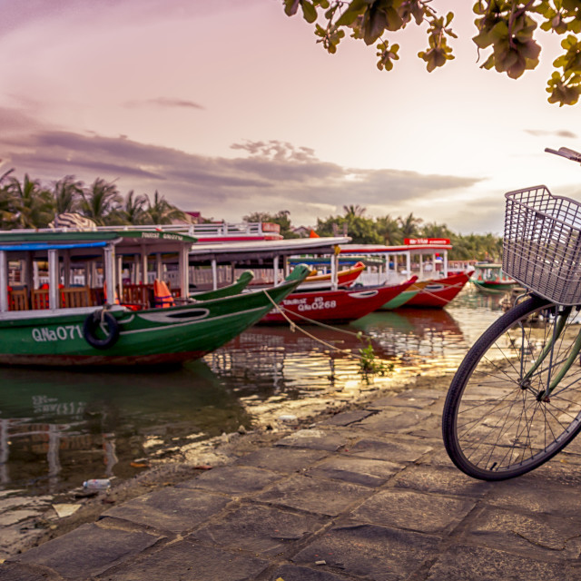 """Hoi An bicycle, river and boats at sunset"" stock image"
