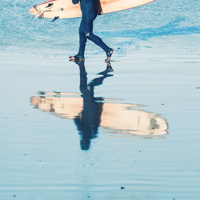 """Surfer in a wetsuit walking along shoreline of beach with his reflection in the sand"" stock image"