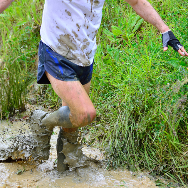 """Unrecognizable man running in mud"" stock image"