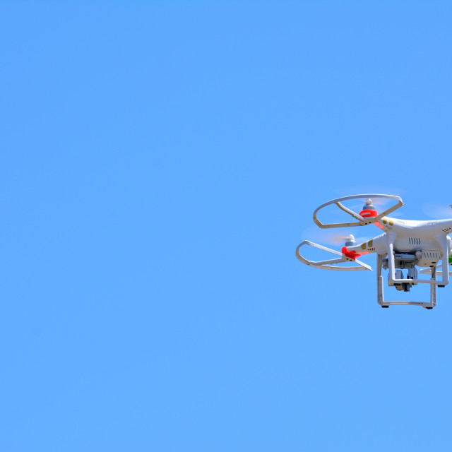 """Flying quadcopter in clear blue sky"" stock image"