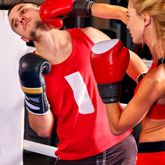 """""""Female boxer throwing right cross at mitts"""" stock image"""