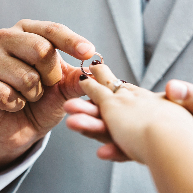 """A couple exchanging rings during a wedding"" stock image"