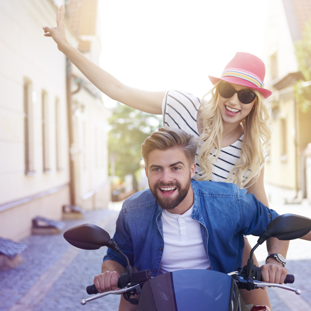 """""""Couple driving a scooter through the city"""" stock image"""