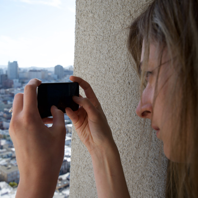 """A tourist woman photographs a city with her mobile phone"" stock image"