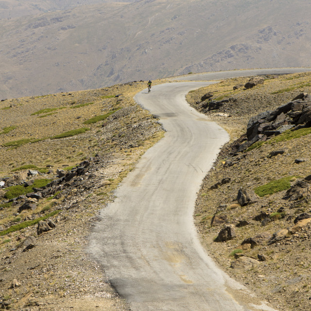 """Man alone in barren mountains biking"" stock image"