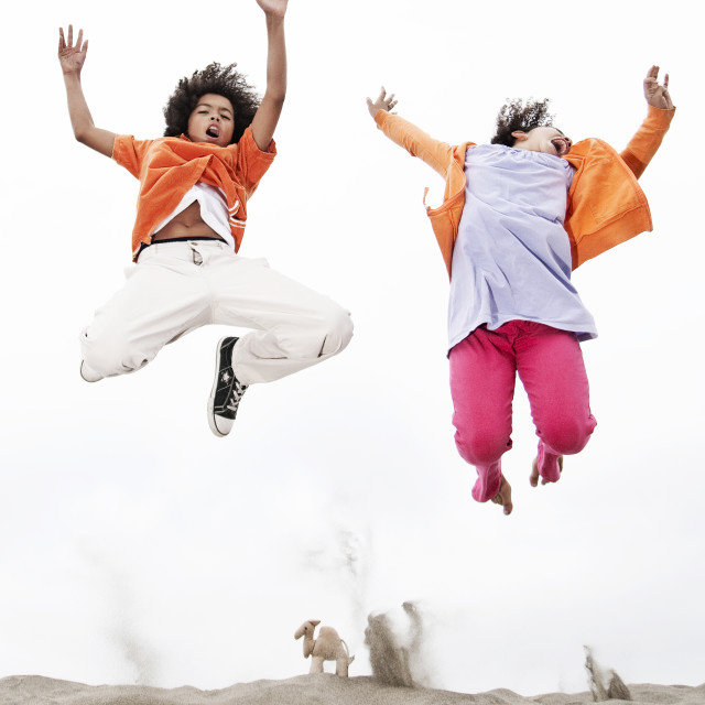 """Kids leap on a beach"" stock image"