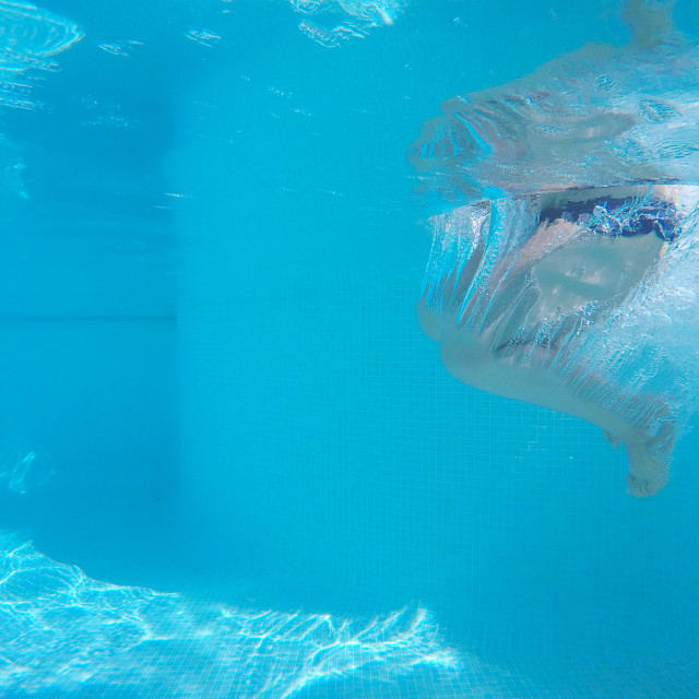 """Underwater shot of unrecognizable person's legs in swimming pool.Clear blue water"" stock image"